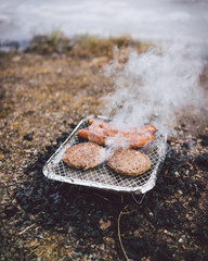 Hamburgers and sausages on the grill in nature