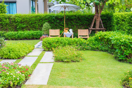 a beautiful wooden table set and big umbrella in the garden at afternoon.