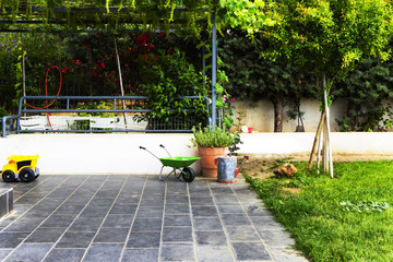 Garden of modern home, in spring, family personal items visible, grass, vines, flowers, gardening tools, garden furniture