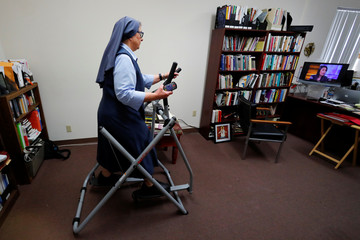 Sister Rose Pacatte, a Catholic nun who reviews movies, watches TV as she works out in her office in this picture taken May 24, 2018 in Culver City, California