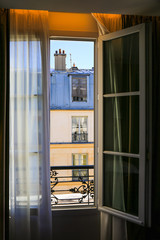 Window overlooking traditional french old house with typical balconies, rooftops and chimney pots.