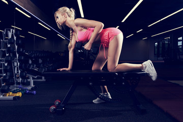 Beautiful female model with long braid, dressed in sports pink bra, shorts and white trainers, performing one arm bent-over dumbbell row with bench used as support. Sexy woman lifting weight in gym.
