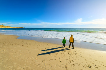 Two boys standing at the beach