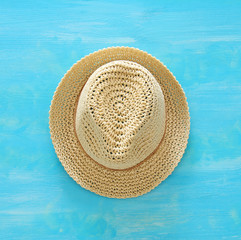 vacation and summer image with fedora beach hat over blue wooden background.