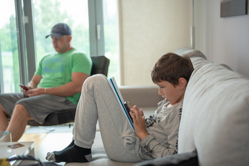 Young boy sitting in living room, looking to smartphone and drawing, with his father in the background