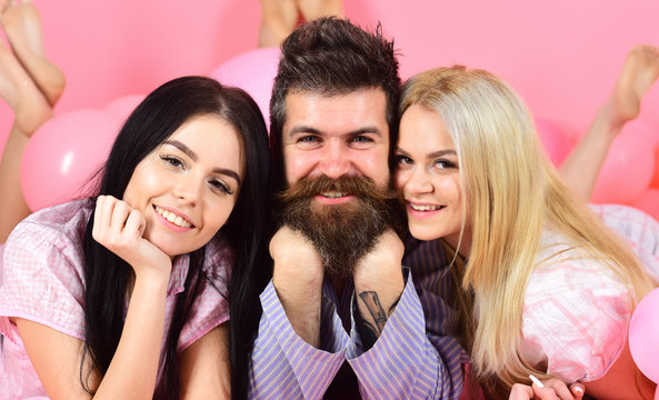 Girls fall in love with bearded macho, pink background. Threesome on smiling faces lay near balloons. Alpha male concept. Man with beard and mustache attracts blonde and brunette girls.