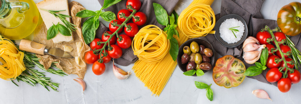 Italian food ingredients with pasta, tomatoes, cheese, olive oil, basil