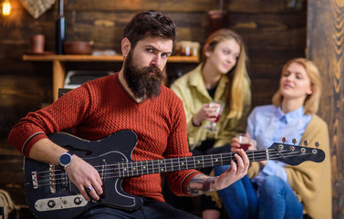 Guitarist rehearsing new show. Bearded man entertaining his wife and daughter with lovely tunes. Rock musician on vacation with family in countryside. Man with stylish hipster beard playing guitar