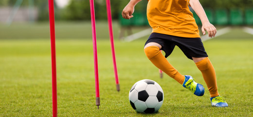 Soccer Player with Soccer Ball Running Slalom Around Training Sticks. Football Speed Training. Young Footballer in Yellow Sportswear at Training Session on Grass Soccer Field