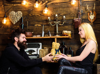 Man give to lady teddy bear as gift on anniversary. Anniversary concept. Couple in love on smiling faces enjoy holiday. Couple spend romantic evening in gamekeepers house, wooden interior background