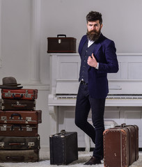Macho stylish on thoughtful face standing near pile of vintage suitcase. Baggage and travelling concept. Man, traveller with beard and mustache with luggage, luxury white interior background.