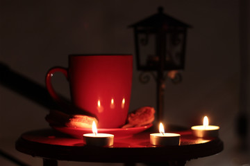 Cup of brewed coffee, a branch of spruce and lantern