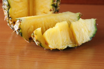 Ripe pineapple and pineapple slices on  wooden