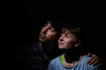 guy with a girl looking up against a dark background. low key