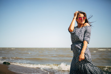 beautiful young woman with black hair in a long dress having fun on the beach of the Azov Sea