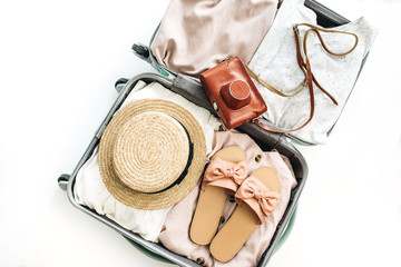 Hand luggage with stylish feminine clothes on white background. Flat lay, top view. Summer travel fashion concept.