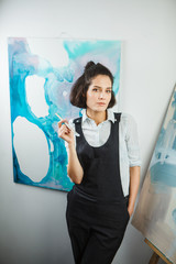 Girl artist in uniform at workshop on background of pictures