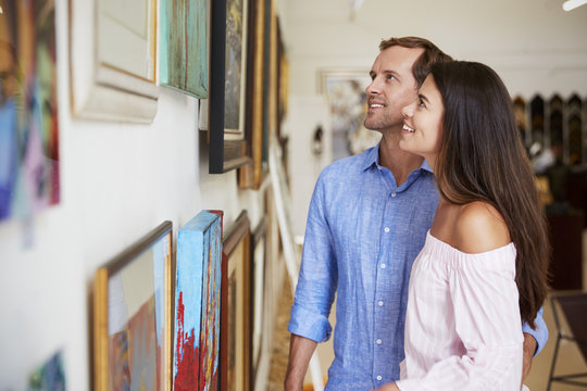 Couple Looking At Paintings In Art Gallery Together
