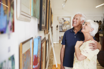 Senior Couple Looking At Paintings In Art Gallery