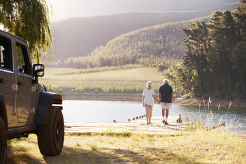 Senior Couple Walking By Lake At The End Of Road Trip