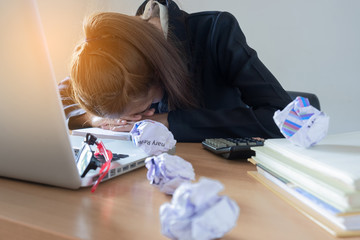 Businesswoman putting his head down on desk in office