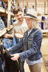 Junges Paar beim Shopping nach Jeans Kleidung