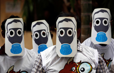 People protest against pollution by wearing cutouts of gas masks on World Environment Day in Mumbai