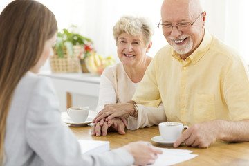 Happy senior man and his wife conversing with financial advisor about loan