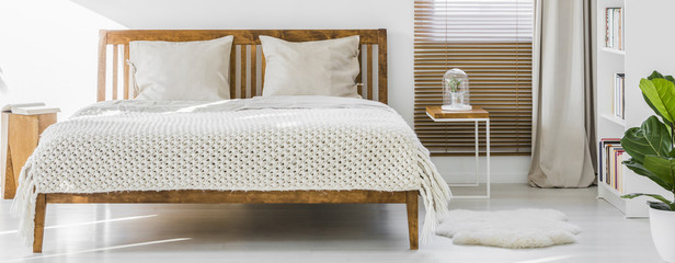 Front view of a simple wooden double bed with cushions and thick weaved cover in a white sunny bedroom interior. Panorama. Real photo.