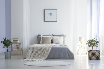 Round rug in front of grey bed with blanket in minimal bedroom interior with poster. Real photo