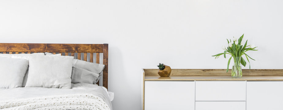 Close-up of a part of wooden bed with linen and pillows and a side cabinet with fresh cut flowers in a vase on top standing against a white wall in a bright bedroom interior. Panorama. Real photo.
