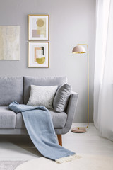 Real photo of a grey couch with pillows and blanket standing next to a gold lamp and a wall with paintings in living room interior