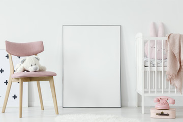 Plush toy on pink chair next to poster with mockup in baby's room interior with bed. Real photo. Paste your poster here