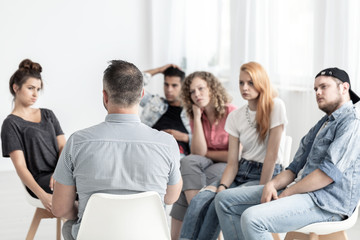 Group of young people talking with psychologist in the rehab center