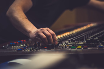 Hand of the mixing engineer on the audio console