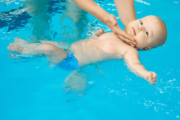 Happy little baby swimming in water pool with help from mothers hands.