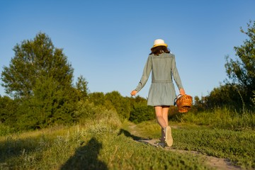 Outdoor summer portrait of teen girl with basket strawberries, straw hat. A girl on country road, back view.
