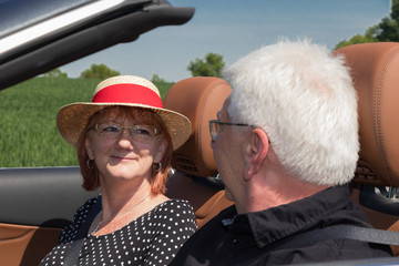 happy older couple drives with a luxury convertible car
