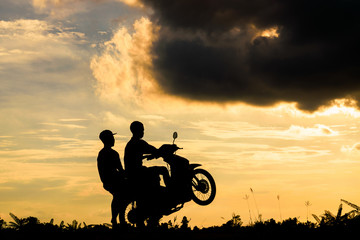 Two boys riding a motorcycle by lifting the front wheel with the orange sky in background. Extreme action of two boys riding a motorcycle.