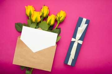 Bouquet of yellow roses, envelope and gifts. Congratulation, holiday, lifestyle concept. Space for a text. Top view. Close up.