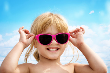 the little girl puts on pink sunglasses and laughs. The portrait on the sky background.