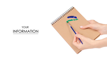 Notepad for drawing and paint brush in hand pattern on white background isolation