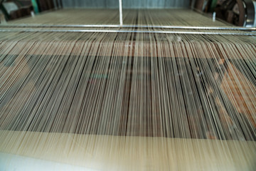 Silk threads on weaving machine. Vietnamese handmade silk producing