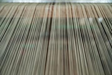 Silk threads on weaving machine. Vietnamese handmade silk producing