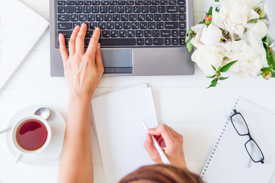 Workspace with girl's hand on laptop keyboard and writing in notebook with empty blank, cup of tea, glasses, white peony on woodden table. Top view feminine office desk. Freelancer working place.