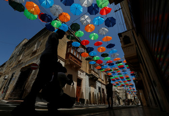 People pose for pictures under a canopy of coloured umbrellas hanging over a street in preparation for a music festival at the weekend, in Zabbar