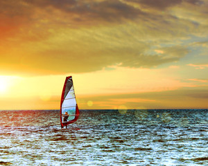 Windsurfer in the sea with a scenic sunset sky. Toned, lens sun flare. Active sport vacation concept