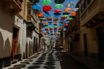A man takes pictures under a canopy of coloured umbrellas hanging over a street in preparation for a music festival at the weekend, in Zabbar