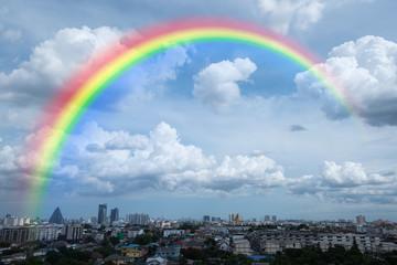 rainbow in cloudy sky over city