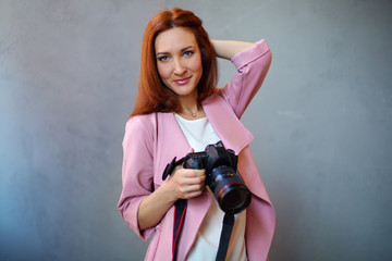 Young cheerful photographer working in studio. Female photographer on gray background.